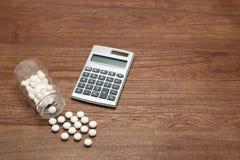 溢出在一个透明医学瓶和计算器外面的白色药片在木头 免版税库存照片
