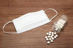 溢出在一个透明医学瓶和面具外面的白色药片在木头 图库摄影