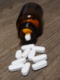 溢出在木桌上的一个药瓶外面的白色药片 免版税库存照片
