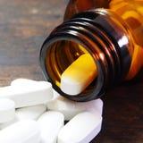 溢出在木桌上的一个药瓶外面的药片 库存图片