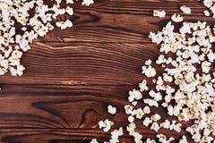 溢出在玉米花边缘在木棕色背景的 图库摄影