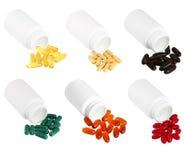 溢出在白色塑料医学瓶外面的一套药片 免版税图库摄影