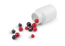 溢出在药瓶外面的莓果 免版税库存图片