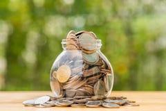 溢出在金钱瓶子外面的泰铢硬币 免版税库存图片