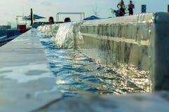 溢出游泳池边缘  水小瀑布 免版税库存图片