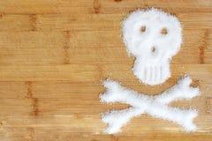 溢出的白糖水晶建议的致命的糖瘾形成在一张木桌上的一块头骨 免版税图库摄影