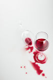 溢出的红葡萄酒在玻璃和隔绝在白色 库存照片