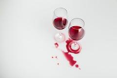 溢出的红葡萄酒在玻璃和隔绝在白色 免版税库存照片