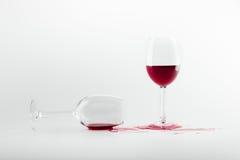 溢出的红葡萄酒在玻璃和隔绝在白色 免版税库存图片