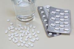 溢出的药片、医药片剂和水在白色背景 免版税库存图片