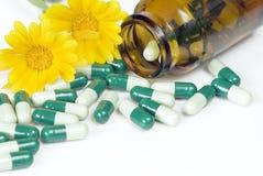 溢出的药片、瓶和两个桔子万寿菊花 免版税库存照片