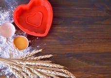 溢出的蛋面粉木背景与麦子和烘烤盘卵黄质茎的  库存照片