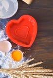 溢出的蛋面粉木背景与麦子和烘烤盘卵黄质茎的  库存图片