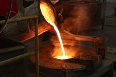 溶解的铁从杓子倾吐入熔化炉 图库摄影