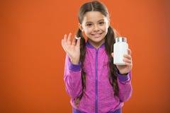 滋补饮食帮助身体是健康的 女孩长发举行药片和塑料瓶 维生素概念 需要维生素 免版税库存照片