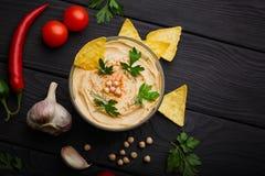 滋补hummus一张顶视图在一个玻璃碗和菜的 与烤干酪辣味玉米片的阿拉伯盘在黑木背景 免版税库存照片