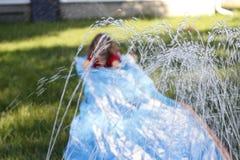 滑下来一张室外滑动和幻灯片的微笑的女孩 在水的选择聚焦在孩子前面 库存图片