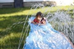 滑下来一张室外滑动和幻灯片的微笑的女孩 在水的选择聚焦在孩子前面 免版税库存图片
