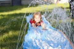滑下来一张室外滑动和幻灯片的微笑的女孩 在水的选择聚焦在孩子前面 免版税库存照片