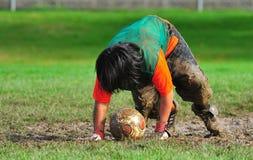 滑倒足球青年时期的守门员泥 免版税图库摄影