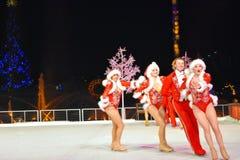 滑冰与专业人的肉欲的圣诞老人妇女的在冰上表演的圣诞节在国际推进地区 免版税库存图片