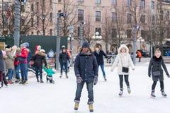 滑冰在一个公开滑冰的溜冰场的一个年轻人户外在城市 图库摄影