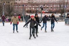 滑冰在一个公开滑冰的溜冰场的几位年轻和老人户外在城市 免版税库存图片