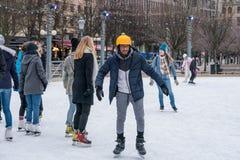 滑冰在一个公开滑冰的溜冰场的年轻人户外在市中心 库存照片