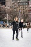 滑冰在一个公开滑冰的溜冰场的年轻夫妇户外在城市 库存照片