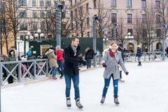 滑冰在一个公开滑冰的溜冰场的年轻夫妇户外在城市 免版税库存照片