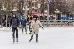 滑冰在一个公开滑冰的溜冰场的年轻夫妇户外 免版税图库摄影