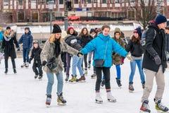 滑冰在一个公开滑冰的溜冰场的愉快的少妇户外 图库摄影