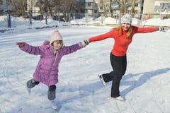 滑冰在一滑冰场的母亲和女儿 免版税库存照片