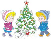 滑冰在圣诞树附近的孩子 免版税库存照片