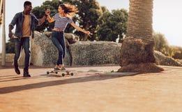滑冰在有朋友的边路的妇女 免版税图库摄影