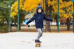 滑冰在秋天公园的孩子 城市样式 开玩笑都市 儿童地方教育局 库存图片