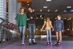 滑冰在路辗的父母和孩子 免版税库存照片