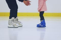滑冰的父亲教的女儿在滑冰的溜冰场 免版税库存图片