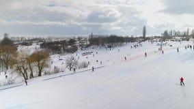 滑在多雪的倾斜下和向上拱与滑雪电缆车的滑雪者和挡雪板天线  影视素材