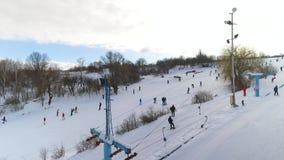 滑在多雪的倾斜下和向上拱与滑雪电缆车的滑雪者和挡雪板天线  股票视频