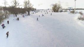 滑在多雪的倾斜下的挡雪板和滑雪者天线  股票录像
