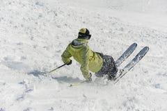 滑在多雪的小山下的后面观点的男性freeride滑雪者 免版税图库摄影