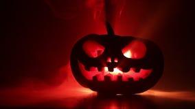 滑子射击 与被雕刻的眼睛的可怕万圣夜南瓜和与灼烧的蜡烛的微笑里面在与火和f的黑暗的背景 股票视频
