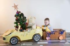 滑稽一点微笑哄骗驾驶有圣诞树的玩具汽车 愉快的孩子以颜色时尚给带来被砍成的xmas树穿衣从 图库摄影