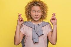 滑稽和逗人喜爱的女孩但愿她的在两只手上的并且保持她的眼睛闭上 她希望 查出在黄色 免版税库存照片
