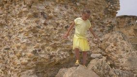 滑稽女孩少年尝试在顶面大岩石做把戏和平衡 股票录像