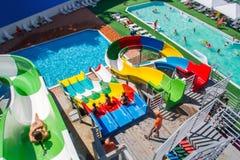 滑稽滑冰与一张幻灯片在水公园 儿童游泳 库存照片