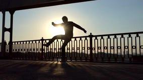 滑稽演员跳舞迪斯科,跃迁,在一座桥梁的日落在Dnipro在Slo Mo 股票录像