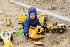 滑稽的两年使用与一个在沙子的大黄色玩具汽车的小孩 春天或秋天照片 免版税库存图片