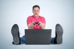 滑稽的人游戏玩家坐使用在膝上型计算机的地板 免版税库存照片